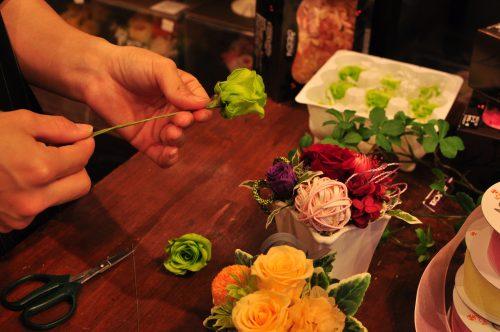 手作業でバラの花に針金とテープでワイヤリング作業を行う