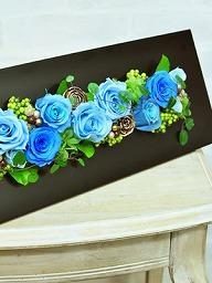 黒いフレームに入ったブルーのバラのアレンジ