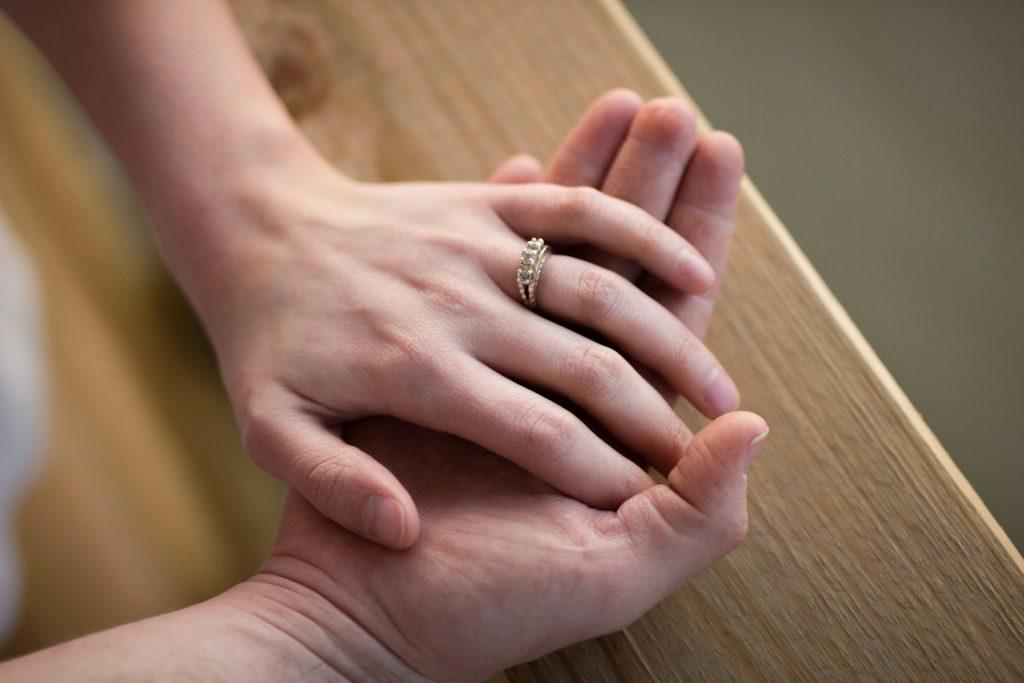 指輪をはめた手を重ねる二人