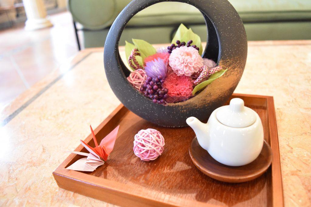 和風の丸い器にピンク色のお花のアレンジメントと急須と折り鶴