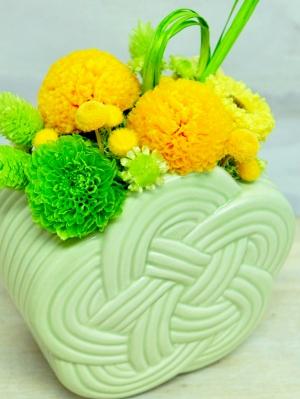 緑色の器に黄色の丸い花と緑色の花が入ったアレンジメント