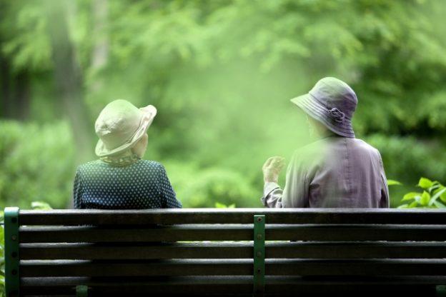 森林の中ベンチで話すお年寄り