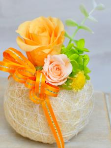オレンジのバラとリボンに丸い玉の器のプリザーブドフラワー
