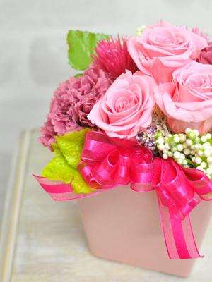 淡いピンクのバラと可愛いピンクのリボンのアレンジメント