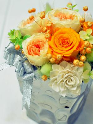 オレンジ、イエローのバラに丸くかわいいリンフラワーのアレンジメント