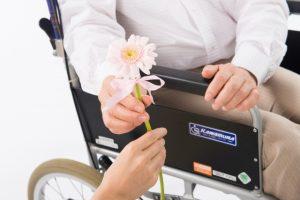 車椅子に乗っているお年寄りへピンクのお花をプレゼント