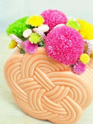 淡いオレンジ色の器にピンクの丸い花や黄色や緑色の花の入ったアレンジ