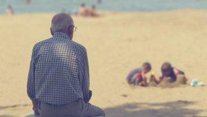 浜辺で遊ぶ子供を見守るお年寄り