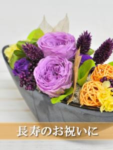 舟型の黒い器に紫の花のアレンジメント