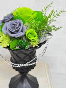 濃いグリーンの花びらのバラとグレーの花びらのバラとを合わせたアレンジメント