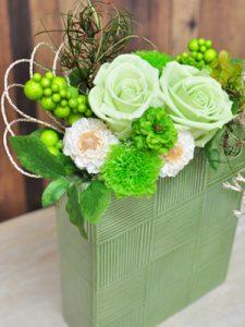 緑色の四角い器にグリーンの花のアレンジメント