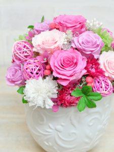 淡いピンクの花びらのバラと白いカーネーションを合わせたアレンジメント