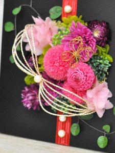 黒いフレームにピンクの花のアレンジメント