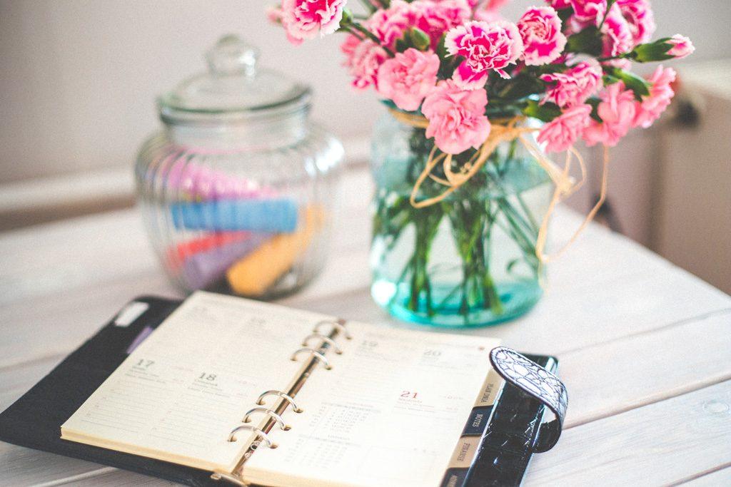 ビジネスマンの手帳とピンクの花