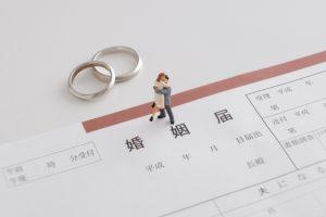 結婚指輪と婚姻届とハグする夫婦