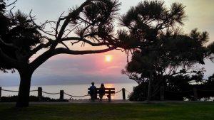 公園のベンチに座り夕焼けを眺めている夫婦