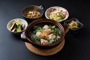 食卓に並んだ鍋料理とおかずの画像