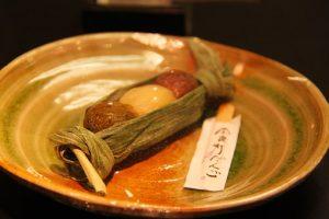 笹の葉に包んだ和菓子の団子の画像