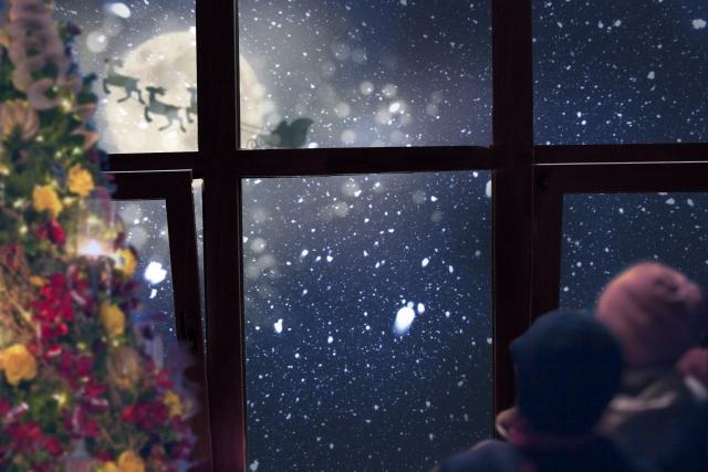 窓から見えるサンタクロースを見る子供
