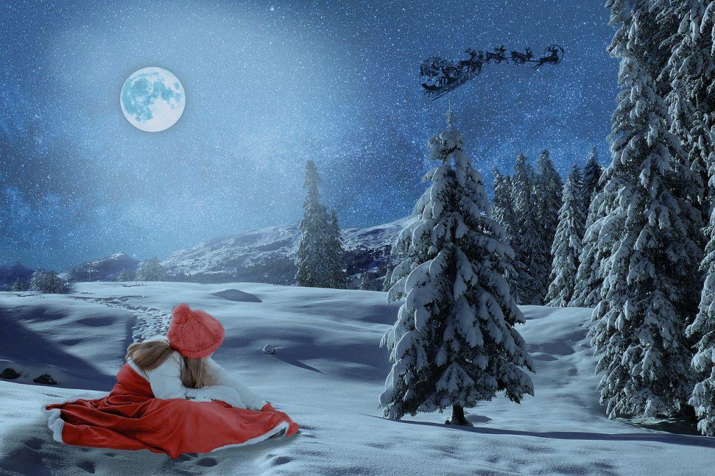 雪の中サンタを見つめる赤い服の女の子