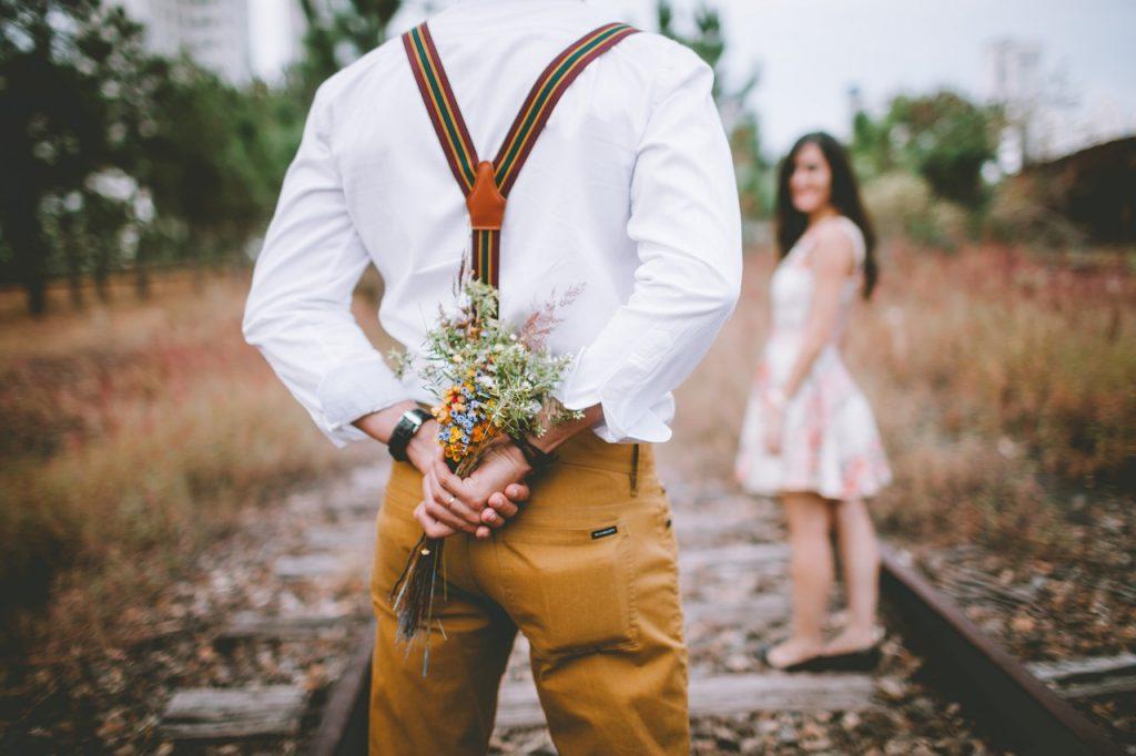女性に花束を渡すために後ろに隠している男性