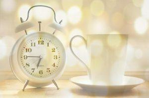 白い時計とコーヒーカップ