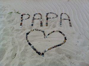 砂浜にパパの文字とハート型を石でかたどる