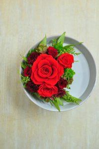 大輪の赤い花びらのバラと葉物を使ったプリザーブドフラワーアレンジメント