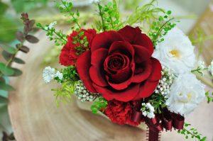 丸く小さな葉と赤い大輪のバラのアレンジメント