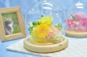 ガラスドーム型の器に黄色い花のアレンジメント