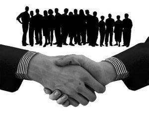 たくさんの人が集まり握手をしている影絵