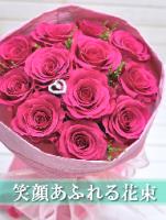 濃いピンクのバラが12本とハートのダイヤピックが入った花束