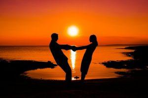 夕日をバックに手を繋ぐカップルの画像