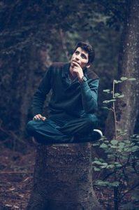 男性が森の木株に座り考えている画像