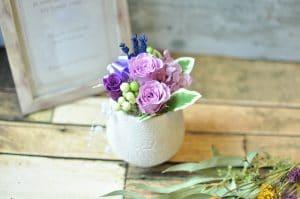 紫の花びらのバラを使ったアレンジメント画像