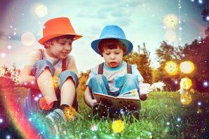 草原で絵本を読む子供の画像