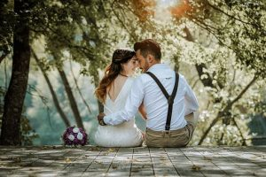 木漏れ日の中、ウェディングドレスを着た女性と白いシャツを着た男性座りながら額同士をくっつけて微笑んでいる