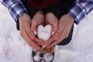 雪の上でカップルが指輪を雪で作った指輪ケースに入れて持っている