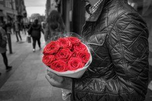 男性が10本の赤いバラの花束を抱えている