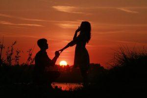 夕日をバックに男性が跪き女性の左手をとってプロポーズしている