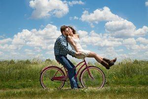 カップルが赤い自転車に乗りハンドル部分に座っている女性が男性の頬にキスしている
