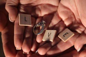 男女の掌の上にL・V・Eと書かれた木のプレートと指輪を置いてLOVEの文字を表現している