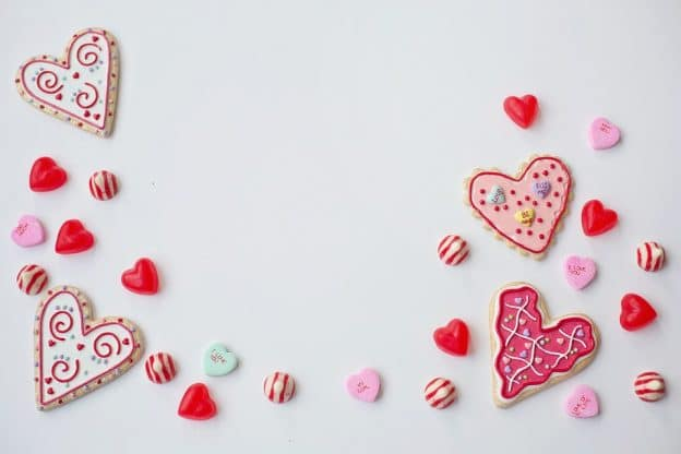 赤・ピンク・白色でアイシングした4枚のハート型のクッキーの周りに同じ色合いのキャンディーなどが置かれている