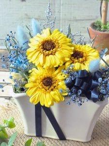 ヒマワリのように大きく咲いたイエローのガーベラとブルーのプリザーブドフラワーやリボンを使用したアレンジメント