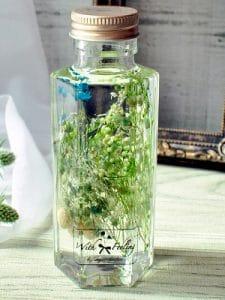 小さな小瓶にグリーンとブルーのプリザーブドフラワーが入ったハーバリウム