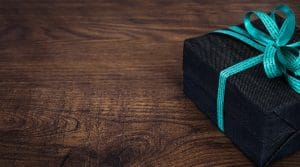 デニム生地のような包装紙にティファニーブルーのリボンがかけられたプレゼントボックスが一つ置かれている
