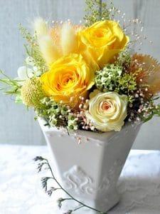 イエローのバラやオレンジのデージーなどでグラデーションになったプリザーブドフラワーのアレンジメント