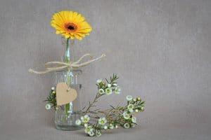 小瓶に生けられた黄色い一輪のガーベラ。瓶の足元には小花が置かれている