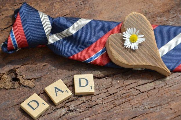 「DAD」と書かれた積木の横にネクタイがありその上にハート型の積み木と花が乗っている